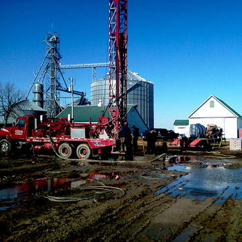 Colored photo of red rotary drilling rig at agricultural site