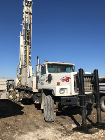 Colored photo of white rotary drilling rig while drilling well