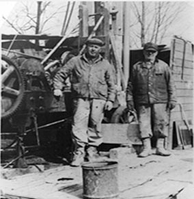 Black and white photo of Max Larson and Malcolm Larson against a cable tool drilling rig