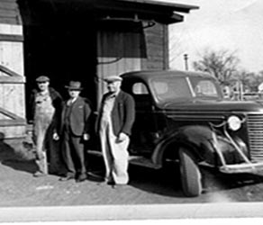 Black and white photo of Malcolm Larson and happy customers against service truck