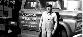 Black and white photo of Malcolm Larson against Larson Well Co. Cable tool drilling rig