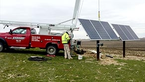 Photo of technician working on solar pump with red service truck in the background.