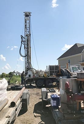 Colored photo of Riley Larson drilling a well at new home construction site